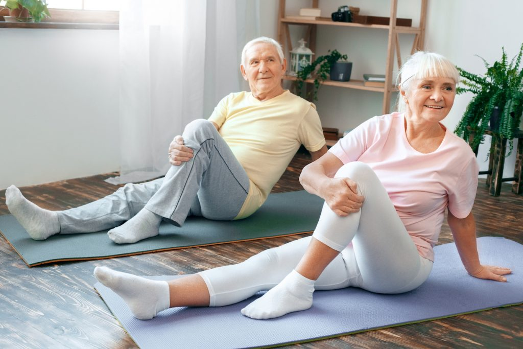 Two elderly people on mats.