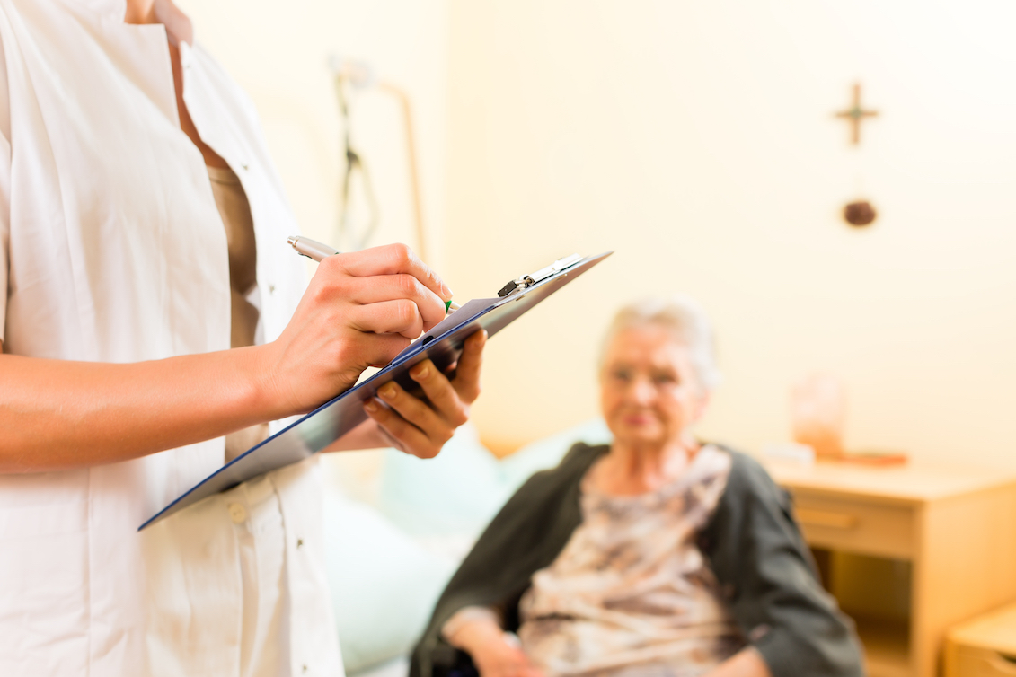A nurse and elderly woman in a health care facility.