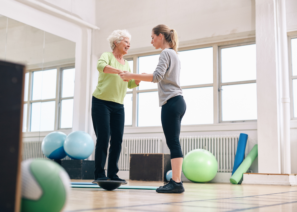 A trainer working with an elderly person.