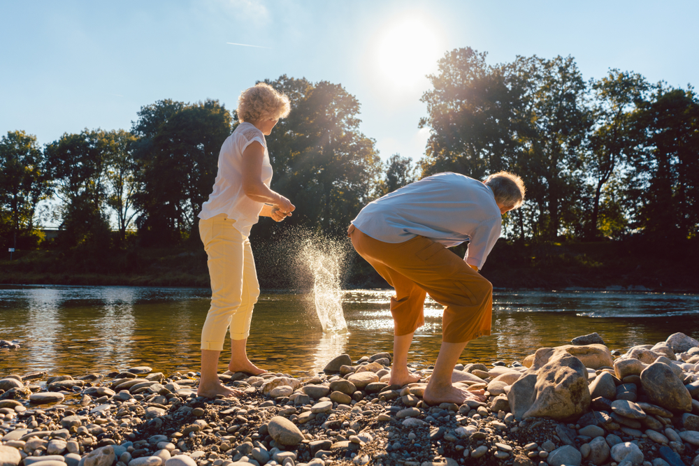 two barefoot senior people enjoying retirement and simplicity while throwing stones into the river in a sunny day