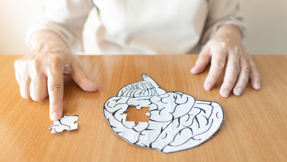 Elderly woman hands putting missing white jigsaw puzzle piece down into the place as a human brain shape