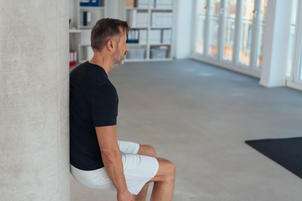 Fit healthy man doing a wall leg sit or squat