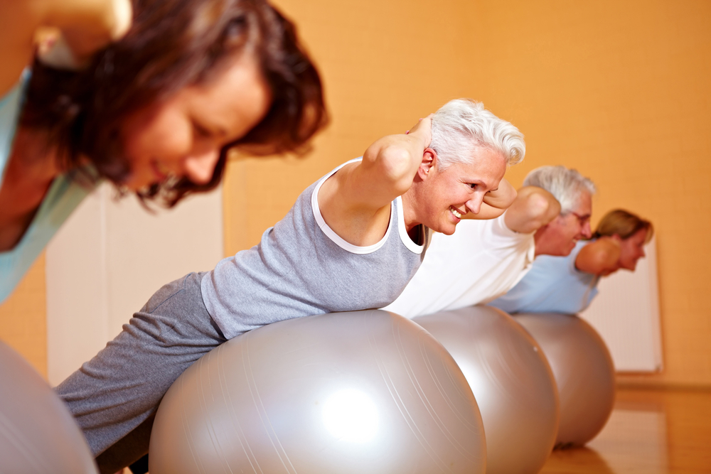 A senior person in a gym doing back exercise on Swiss balls